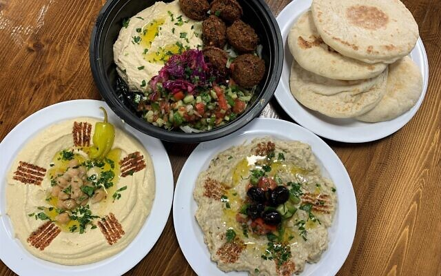 The falafel platter is a popular entrée shown here with fresh-from-scratch hummus and baba ghanoush. Note the creative garnish detail.