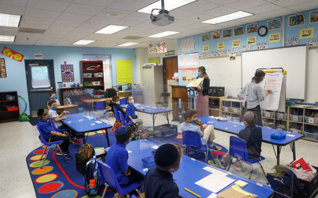 Teachers give lessons to students at Torah Day School of Atlanta, where students are seen wearing masks and sitting behind plexiglass.