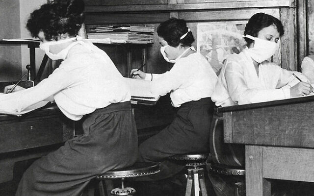 Getty Images // Like today, people wore face masks to work in 1918 to protect against the spread of influenza.