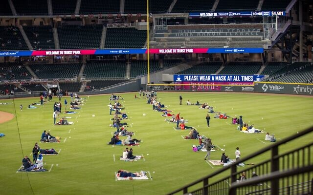 Braves fans sit on the outfield in Truist Park to watch game 5 of the NLCS on the big screen inside of the stadium with a COVID-19 safe experience where pods of people are separated by 16 feet.
