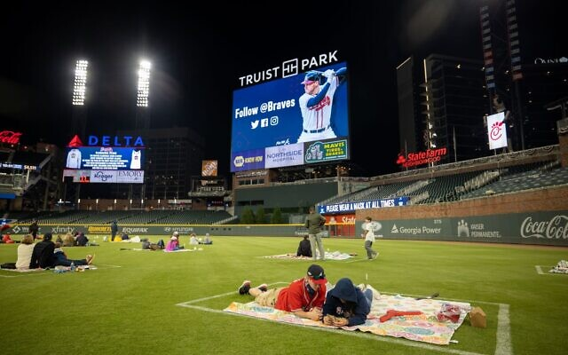 A couple sit on the outfield as part of the Braves' watch party at Truist Park for game 5 of the NLCS.