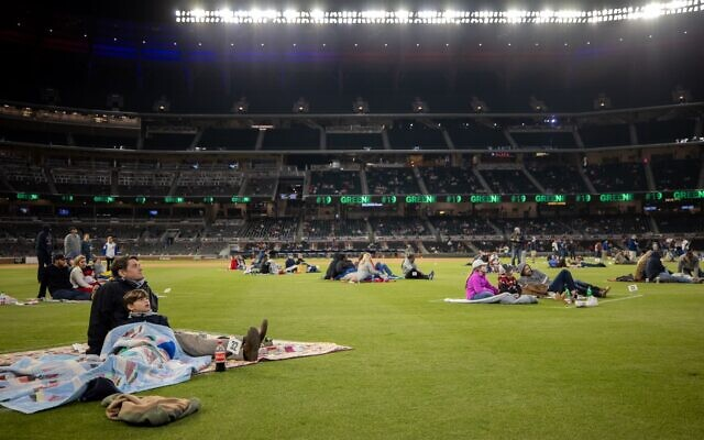 A father and son sit on the outfield as part of the Braves' watch party at Truist Park for game 5 of the NLCS.