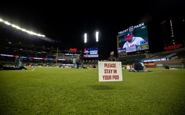 "A sign advises fans to ""please stay in your pod"" on the outfield of Truist Park as fans sit as part of the on-field experience for the NLCS."