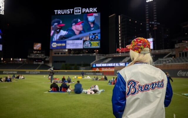 A fan wears a Braves jacket while watching game 5 of the NLCS inside of Truist Park.