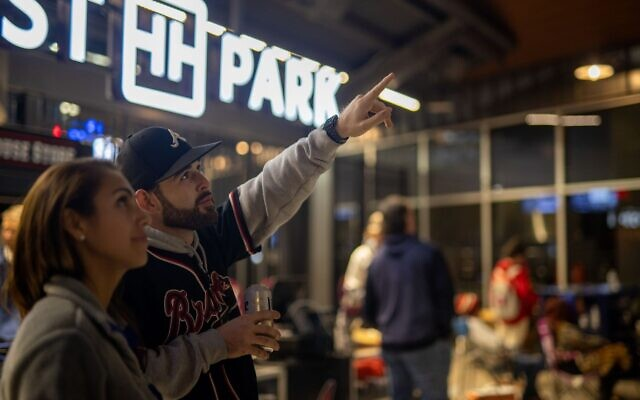 A Braves fan points to the screen where game 5 of the NLCS is being shown, outside of Truist Park.