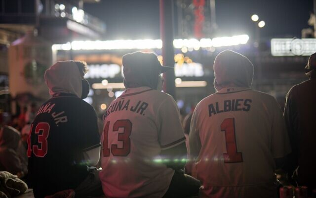 Braves fans, wearing jerseys, sit as they watch game 5 of the NLCS outside of Truist Park on a big screen.