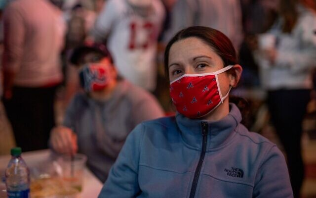 A Braves' fan wears a mask bearing the team's logo while watching game 5 of the NLCS in the Battery outside of Truist Park.