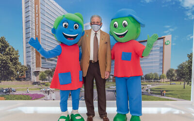 Arthur Blank is committed to giving away at least half of his $6 billion personal fortune during his lifetime. He's pictured here with CHOA's mascots Hope and Will.
