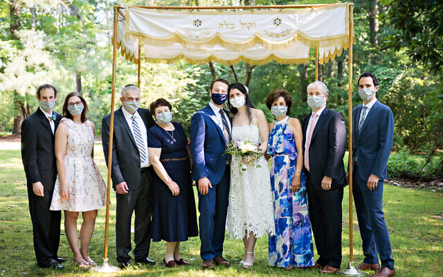 After months of delaying and rescheduling simchas, some resumed by taking health precautions such as being held outdoors or requiring masks. Arthur Oysgelt and Alyse Finkel surrounded by family June 14 in Congregation B'nai Torah's garden.