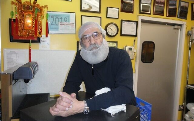 Reuven Michoel Robbins greeting customers at his counter in the Toco Hills Kroger several years ago.