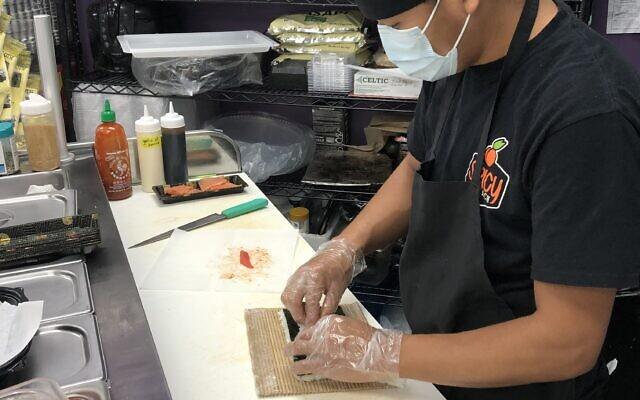 Sushi chef Biak prepares a takeout order request.
