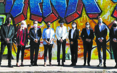 Representatives from nine consulates in Atlanta and representatives from Atlanta city government line up in front of the mural honoring frontline workers in the pandemic.
