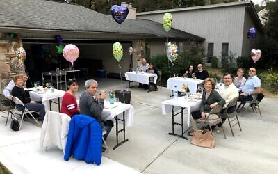 Marlene and Hyman Sukiennik, sitting at third table, enjoy their October birthdays at a party with 10 friends.