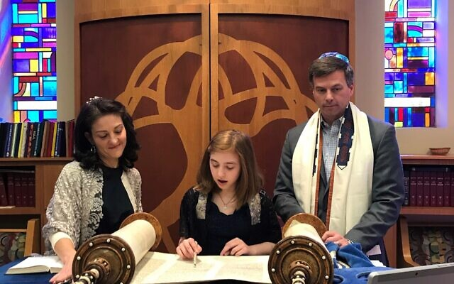 Sari D'Agostino reads from the Torah May 2 in the chapel of Congregation Shearith Israel surrounded by her parents, Annie and Josh.