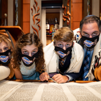 Scensations Photography // Jacob Levin's bar mitzvah was postponed from March to October as a result of the pandemic. Here he poses with his family showing off their personalized masks.