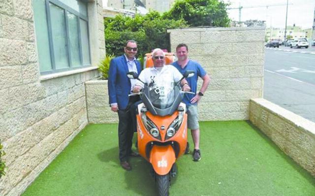Dr. Scheinberg sits on a United Hatzalah ambucycle at their Jerusalem headquarters.
