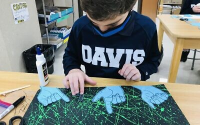 Using American Sign Language, Davis seventh grader Adam places his traced hands in a collage.
