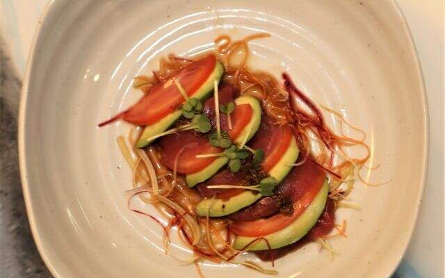 Cuneal-shaped wedges of avocado layered with tomato and raw tuna.
