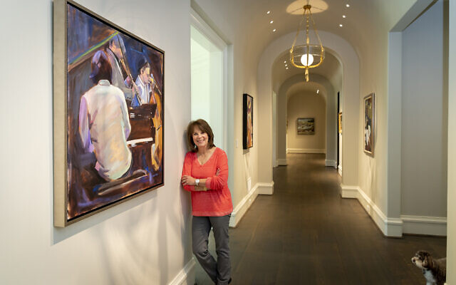 "Diane leans against her painting ""The Jazz Club"" in the long front hall, which serves as a stunning gallery-like backdrop for art. The series of light fixtures are by Baker."