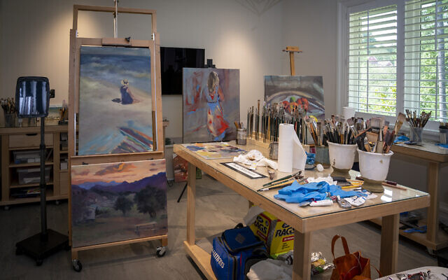 Diane paints in her studio with dimmed lighting.
