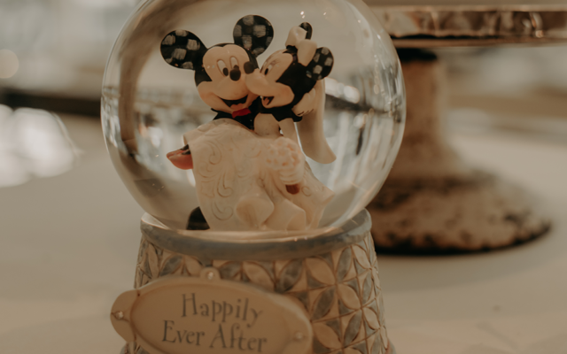 "Nathalia Frykman Photography // A Disney-themed snow globe that reads ""Happily Ever After"" sat on the cake table."