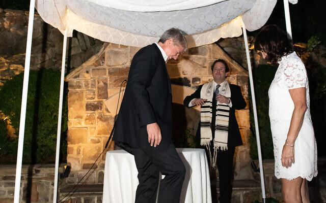 Chip Umstead broke two glasses as Rabbi Brad Levenberg cheered him on.