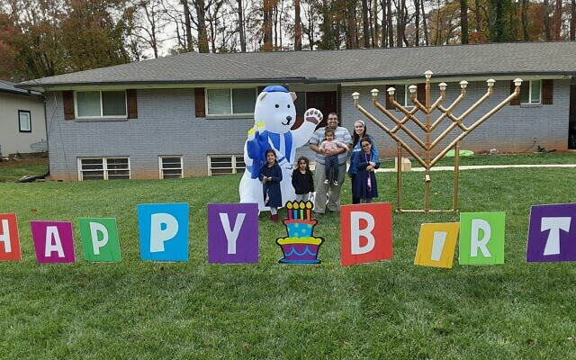 Levi and Aliza Afrah stand with their children Aderet, Ayala, Orli and Nili in front of their menorah, celebrating the three Chanukah birthdays of Aderet, Orli and Nili.