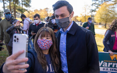Nathan Posner // Jon Ossoff takes a selfie with a young supporter during a march to support  early voting in Gwinnett County on December 14th.