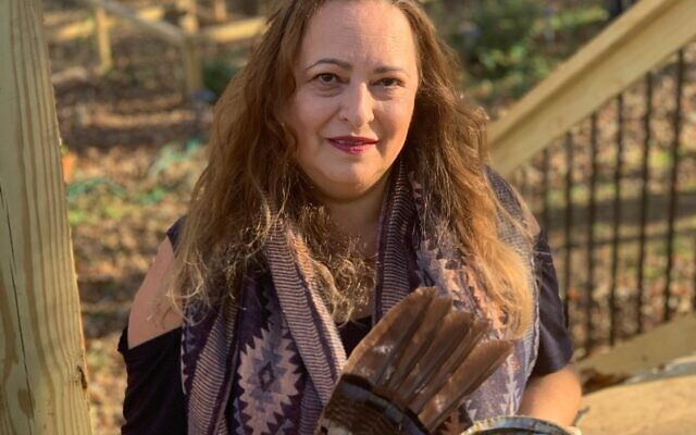 """Tal Moran holds a fan of macaw feathers, used with a """"saging/smudging"""" (purifying) incense mix in an abalone shell she found near the Pacific Ocean."""