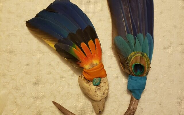 The macaw and peacock feather fan has a deer antler handle, traded to Moran for prized feathers at a powwow (gathering of diverse Native American Indian nations).