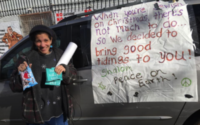 "Rivkah Eidex holds up one of the bags being given to the homeless next to the ""Christzmah"" mobile."