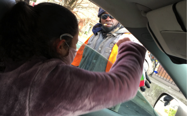 "Tova Eidex hands a bag to the homeless from the ""Christzmah"" mobile."