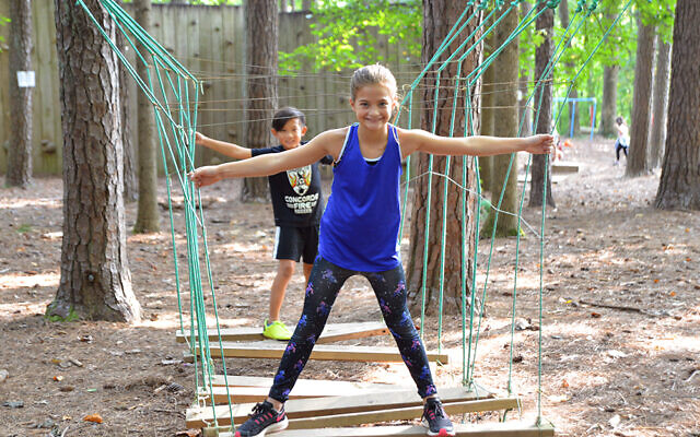 Campers at MJCCA Day Camps balancing on a ropes course.