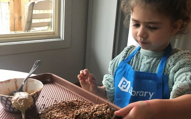 Melanie Katz makes a bird feeder out of a pinecone, bird seed and peanut butter.