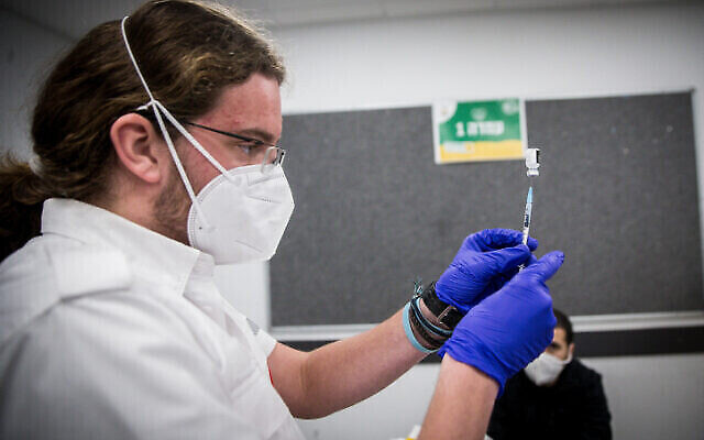 A medical worker prepares a COVID-19 vaccine in Kiryat Ye'arim, on January 25, 2021. (Yonatan Sindel/Flash90)