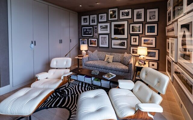 The Pliners converted the guest bedroom into a den where fine photography lines the walls, zebra rug afoot. The white chairs are Eames lounge chairs made of Palisander wood and Polar White leather. The sofa is Holly Hunt.