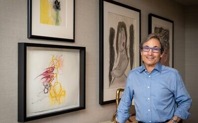 """Photos by Duane Stork // Designer Stuart Pliner poses in his foyer with  (right) Thornton Dial's """"Lady Looking for Shade,"""" 2003 mixed media on paper. Left: Rocio Rodriguez watercolors and oil paintings on paper."""