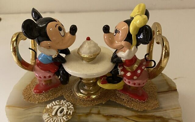 Mickey and Minnie share dessert, sitting in heart-shaped chairs.