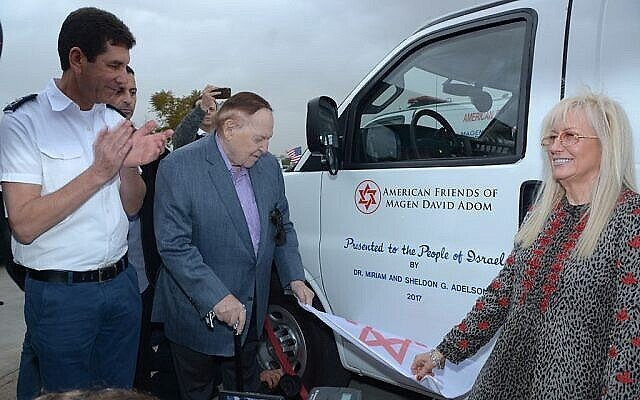 Illustrative: (From left) Magen David Adom Director Avi Bin, Sheldon and Miriam Adelson unveil one of five new bullet proof ambulances that the Adelsons donated to four West Bank settlements. (Courtesy: Magen David Adom)