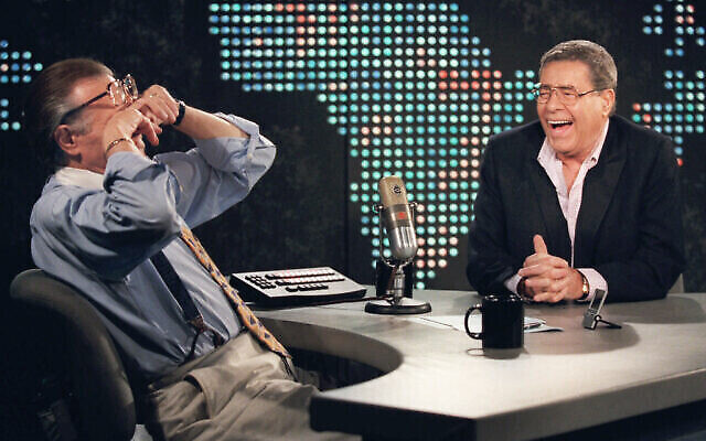 """In this Thursday, Aug. 26, 1999, file photo, talk show host Larry King wipes his eyes after laughing at a joke by comedy legend Jerry Lewis, on the set of """"Larry King Live"""" at CNN Studios in the Hollywood section of Los Angeles.(AP Photo/Chris Pizzello, File)"""