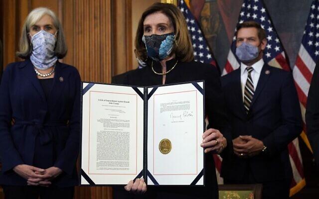House Speaker Nancy Pelosi displays the signed article of impeachment against President Trump on Jan 13. (Alex Brandon / Associated Press)