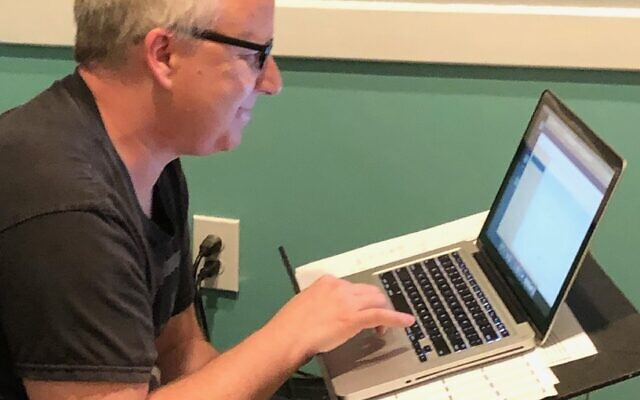 Musician and owner of Sandy Springs Music, Dave Szikman plans out the week's schedule of teaching assignments on his computer.