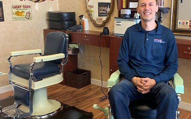 Memorabilia and antiques surround Yury Abramov in his Vintage Barbershop.