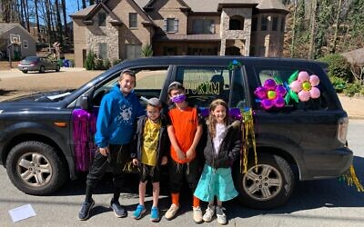 The Wasserman family steps out of their car to pose during the scavenger hunt.