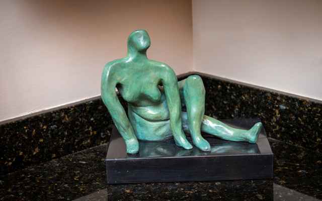 "Aaron's  bronze sculpture entitled ""Turquoise Woman"" sits on a marble base."
