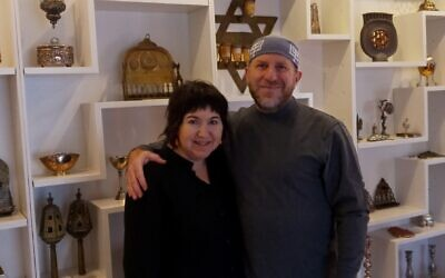 Elihu Siegman and Nancy Sokolove stand in front of a section of their Judaica collection wall.