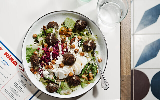 Photo by Angie Webb // A falafel salad with crispy chickpeas, romaine, grape tomatoes. The standout was the homemade green goddess tahini dressing and artful couli presentation.