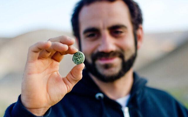 Archaeologist Hagay Hamer holding a Bar Kokhba coin found in the desert. (Yoli Schwartz, Israel Antiquities Authority)