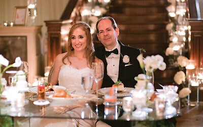 Photos by Laura Stone Photo // The couple listens to wedding toasts at their sweetheart table in front of Summerour's iconic staircase lined with votives.