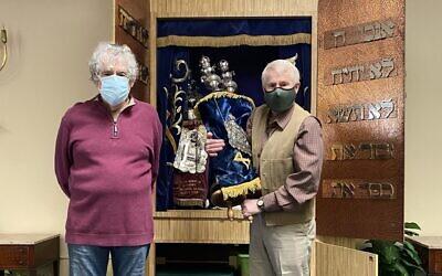 Bernie Wolfson of Congregation Beth Sholom in Gulfport, Fla., hands over Torah to Howard Winkler of Jewish Congregation of Blue Ridge.